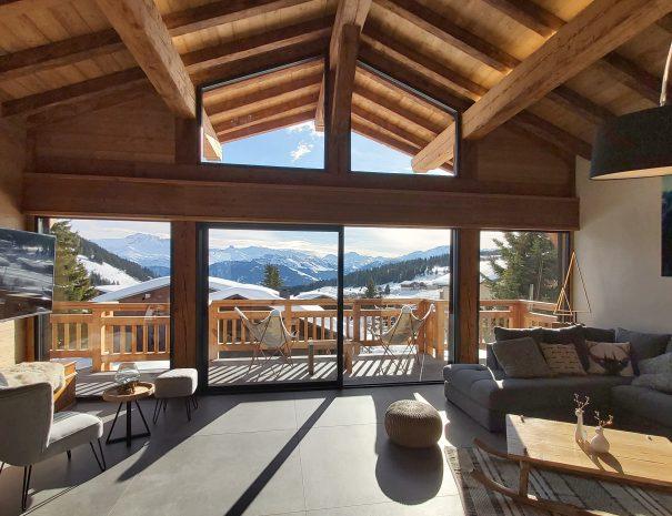 Salon avec cheminée et vue panoramique sur les pistes de ski Les Saisies